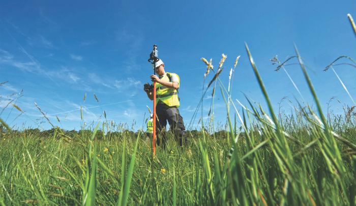green-field-blue-sky-engineer-measuring